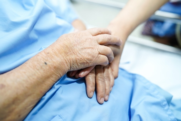 Touching hand asian senior or elderly old lady patient with love, care, encourage and empathy.