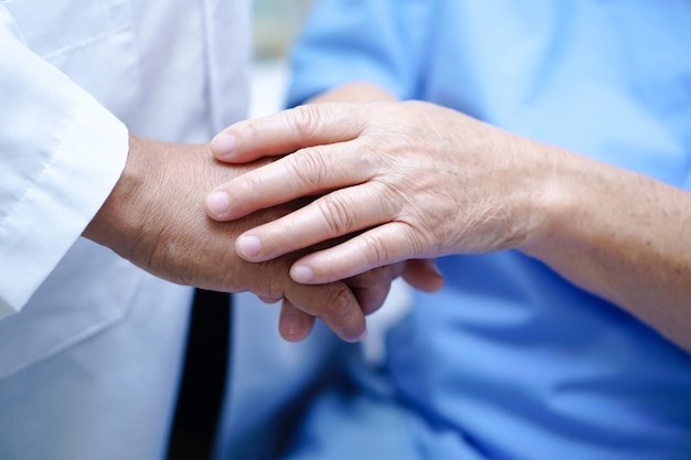 Touching hand asian senior or elderly old lady patient with love, care and encourage.
