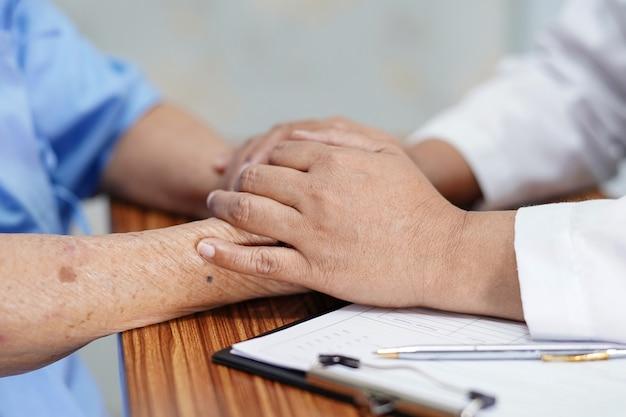 愛をこめてアジアシニア女性患者に触れる。