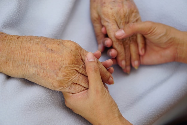 Touching or holding hands asian senior