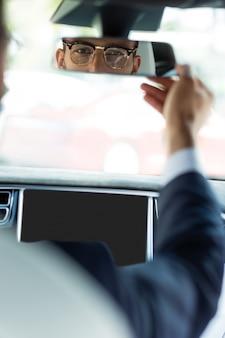 鏡に触れる。運転する前にバックミラーに触れるハンサムな青年実業家