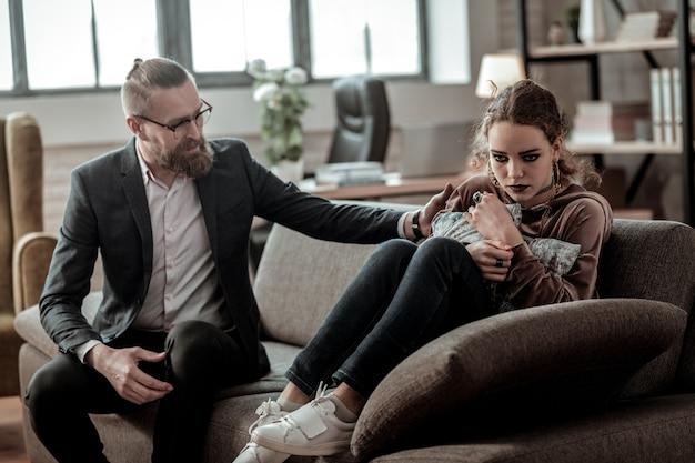 肩に触れます。非常にストレスを感じている娘の肩に触れるひげを生やした愛情のある父親