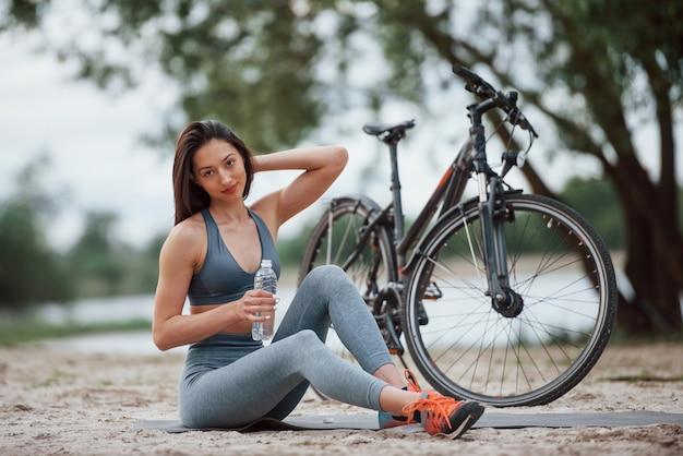 Касаясь волос. велосипедистка с хорошей формой тела сидит возле своего велосипеда на пляже в дневное время