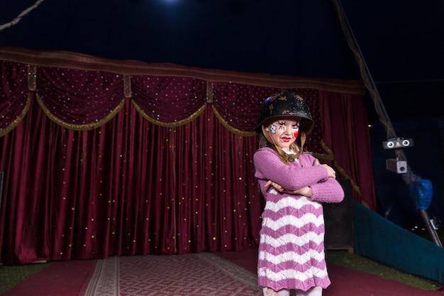 Суровая девушка в боевом шлеме и полосатом платье уверенно стоит со скрещенными руками на сцене с красным занавесом