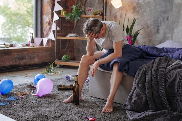 Тяжелое утро. измученный зрелый мужчина сидит на кровати и смотрит вниз