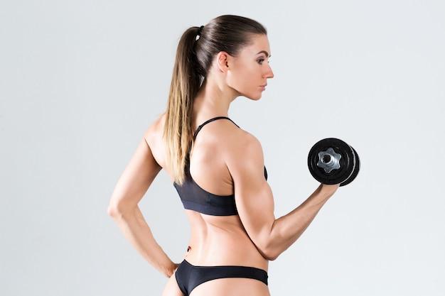 Жесткая молодая женщина, стоя на сером фоне. мускулистая женщина делает упражнения.