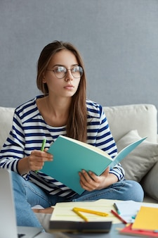 Заботливая красивая журналистка держит синий блокнот и ручку, пишет статью, носит круглые прозрачные очки, сидит дома на диване