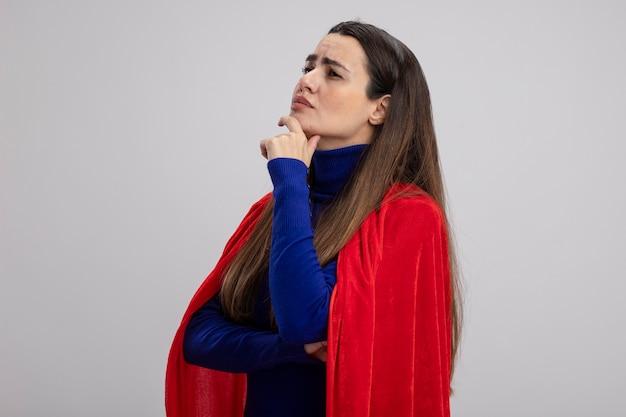 Задумчивая молодая девушка супергероя, смотрящая на бок, схватившись за подбородок, изолирована на белом