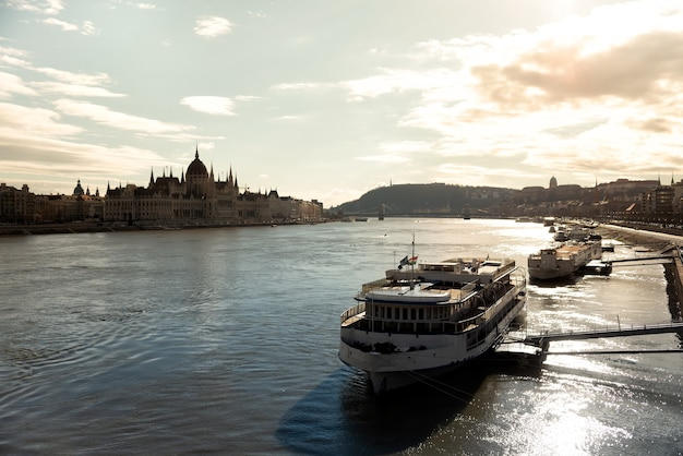 Tour boat on the danube with silhouette of parliament on the background. budapest, hungary