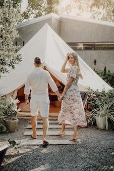タイでのツアー。タイでの新婚旅行を祝う夫と妻のカップル。女性は振り返り、夫の手を握って微笑む。