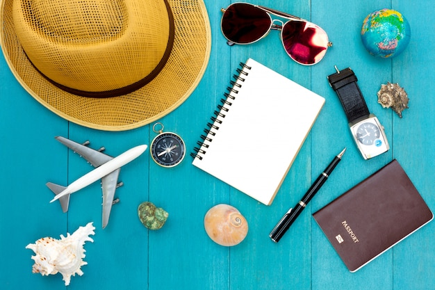 Tour planning of travelling accessories on blue wooden background