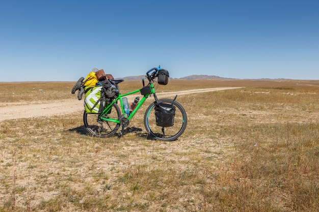 Touring bike full loaded standing on a dirty road tourist bike with bags mongolian steppe