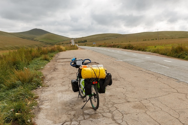 Touring bike stands near the asphalt road in the mongolia