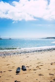 Концепция туризма и летних каникул с парой обуви на песке на пляже у синей морской воды и под красивым небом