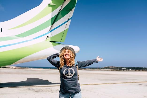 観光と観光旅行の幸せな人々のコンセプトは、機体を持って出発し、休暇の目的地に飛ぶ準備ができている明るく楽しい大人の美しい女性