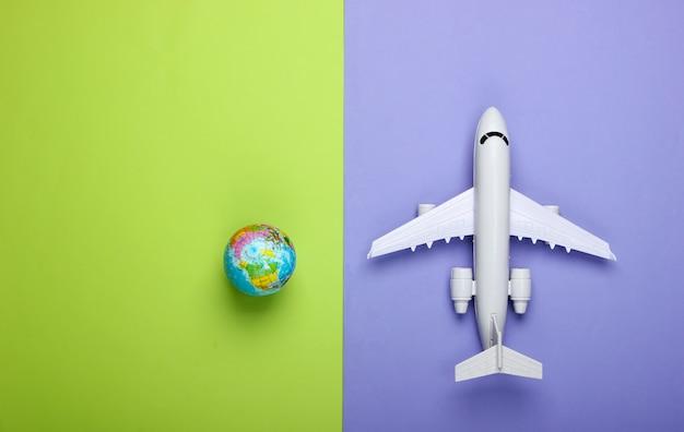 Концепция туризма и путешествий. эмиграция. фигурка глобуса и пассажирского самолета на фиолетовой зеленой стене взгляд сверху. плоская планировка