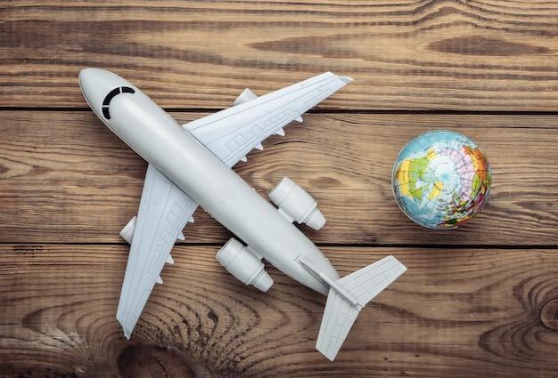 Концепция туризма и путешествий. эмиграция. фигурка глобуса и пассажирского самолета на деревянном столе. вид сверху. плоская планировка