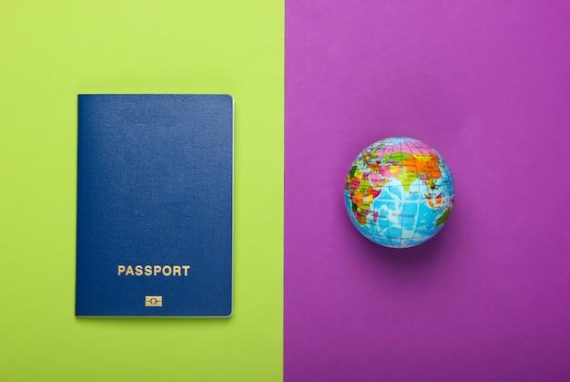 Концепция туризма и путешествий. эмиграция. глобус и паспорт на фиолетовой зеленой стене вид сверху