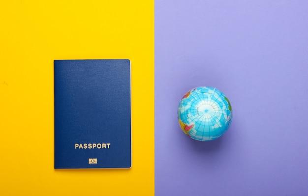 Концепция туризма и путешествий. эмиграция. глобус и паспорт на фиолетовой желтой стене взгляд сверху. плоская планировка
