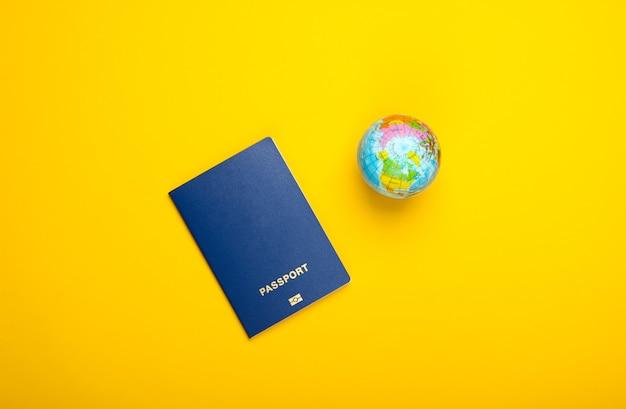 Концепция туризма и путешествий. эмиграция. глобус и паспорт на желтой стене вид сверху. плоская планировка
