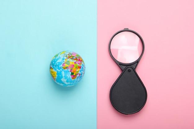 観光と旅行のコンセプト。青ピンクのパステルカラーの壁に地球儀と拡大鏡上面図