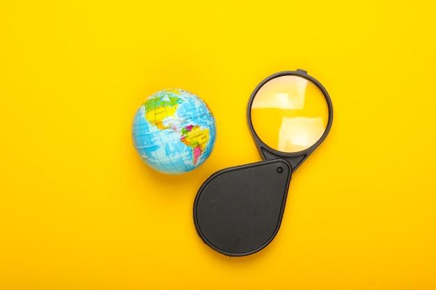 観光と旅行のコンセプト。黄色い壁の地球儀と拡大鏡上面図