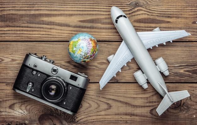 Концепция туризма и путешествий. глобус, фотоаппарат и фигурка пассажирского самолета на деревянной табличке. вид сверху. плоская планировка