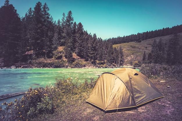 관광 및 여행 개념입니다. 산과 관광 텐트가 있는 아름다운 여름 풍경. 노란색은 산속의 호수 근처에 있습니다. 산에서 밝고 화창한 날.