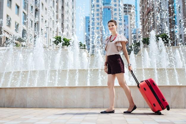 Туризм и путешествия. приятная молодая женщина, держащая чемодан во время поездки в новый город