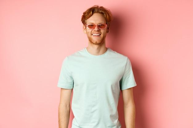 관광 및 휴가 개념입니다. 선글라스와 티셔츠를 입은 쾌활한 빨간 머리 수염 남자, 웃고 분홍색 배경 위에 서 있는 카메라를 보고 행복해 보인다