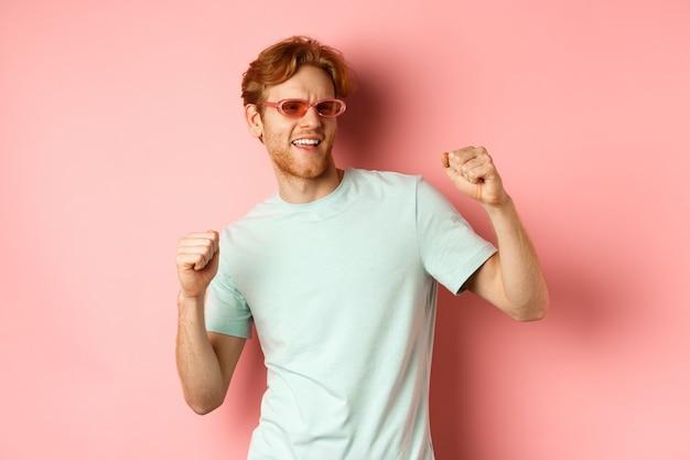 観光と休暇の概念。パーティーで楽しんで、ダンスと休日を楽しんで、ピンクの背景にサングラスとtシャツで立っている陽気な赤毛の男。