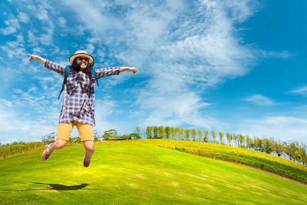 Tourism backbacker woman enjoy jumping on green meadow and nice blue skyl.