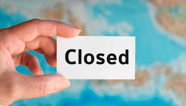 Туризм закрыт - текст на белом листе с глобусом на фоне карты атласа