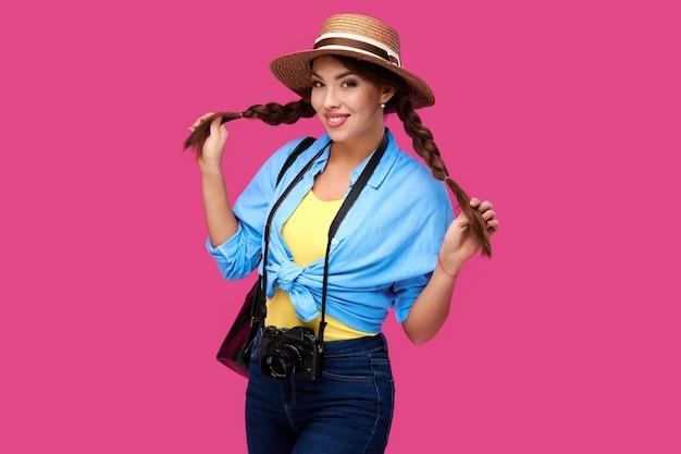 Концепция туризма. возбужденный молодой кавказский турист женщины с фотоаппаратом, изолированным на розовом фоне. битник студентка в повседневной одежде и соломенной шляпе