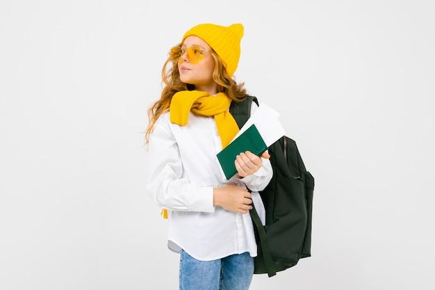 観光コンセプト。バックパック、スカーフ、帽子、パスポートとコピースペースを持つ白いスタジオのチケットで幸せな魅力的なティーンエイジャーの女の子