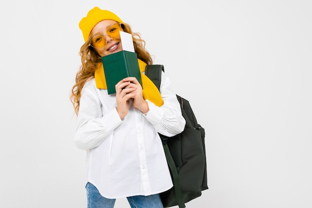 観光コンセプト。バックパック、スカーフ、帽子、パスポートと白いスタジオのチケットで幸せな魅力的なティーンエイジャーの女の子
