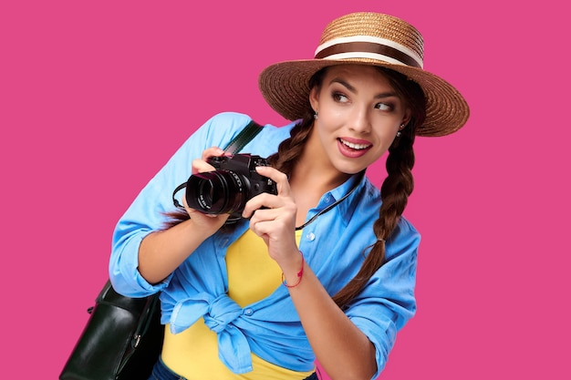 Tourism concept. happy caucasian woman tourist in summer casual clothing holding photo camera, isolated on pink background with copy space