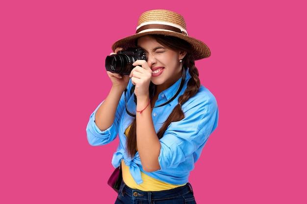 Концепция туризма. счастливая улыбающаяся женщина-турист в летней повседневной одежде, держащая фотоаппарат и фотографирующая, изолированная на розовом фоне с копией пространства