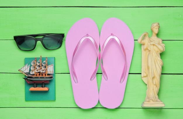 Концепция туризма. фон путешественника. путешествуйте по миру, стиль плоской планировки. туристические аксессуары, сувениры на синем деревянном фоне. вид сверху