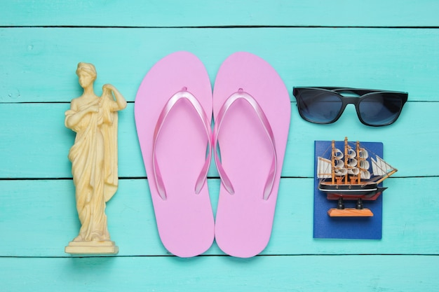 観光の概念。旅行者の背景。フラットレイスタイルで世界中を旅しましょう。観光アクセサリー、青い木製の背景のお土産。