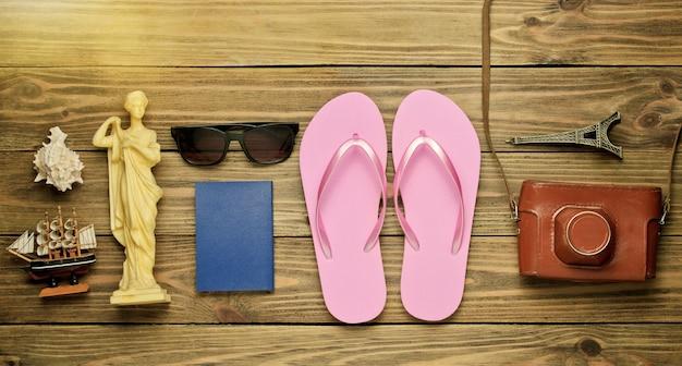 Концепция туризма. фон путешественника. путешествуйте по миру, стиль плоской планировки. туристические аксессуары, сувениры на деревянных фоне. вид сверху