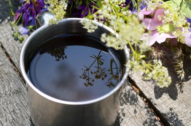 お茶の入ったツーリズムカップ、表面のお茶は花の反射です
