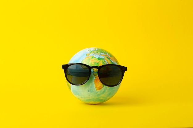 Tourism, ecology, vacation and globalism concept. globe in sunglasses on a yellow background.