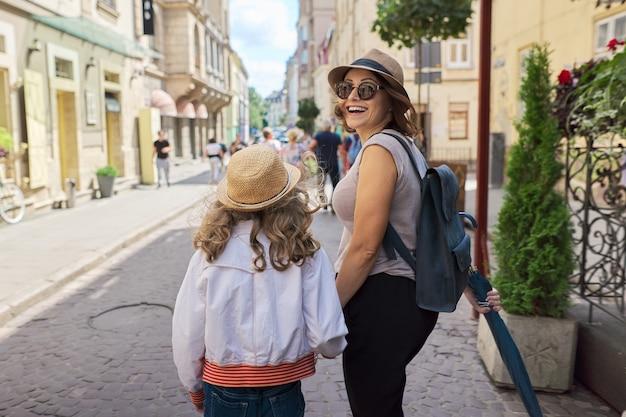 Туризм, семейный отдых, отношения. мать и дочь ребенка, взявшись за руки, гуляют в старом туристическом городе, вид сзади