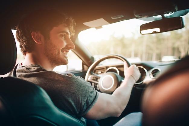 観光-幸せな若い男性と女性幸せは車に座っています。旅行と冒険のコンセプト。