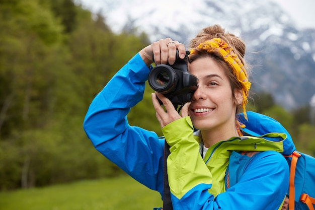 Tourism, hobby and adventure concept. positive young tourist takes picture of scenic landscape on professional camera