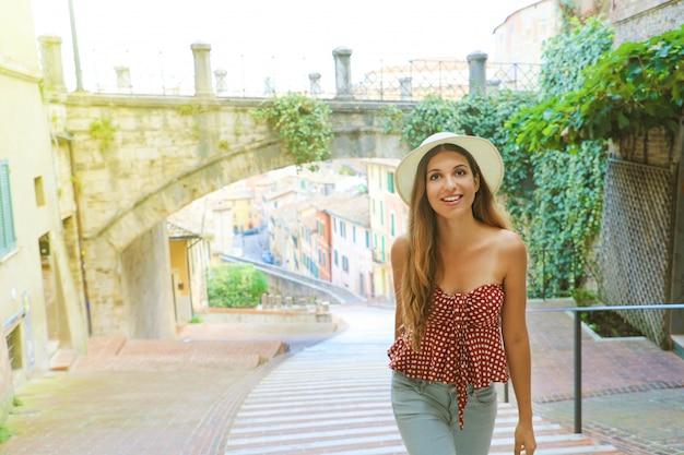 イタリアの観光。ペルージャの古い中世の町を訪れる美しいファッションの少女。
