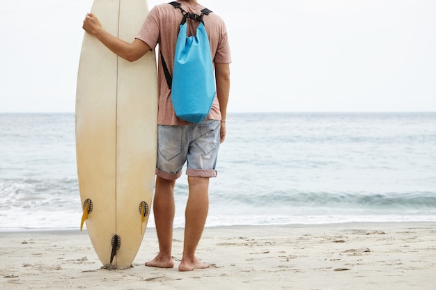 Tourism, leisure and healthy lifestyle concept. back view of young surfer standing barefooted on sandy shore, facing vast ocean and holding his surfboard