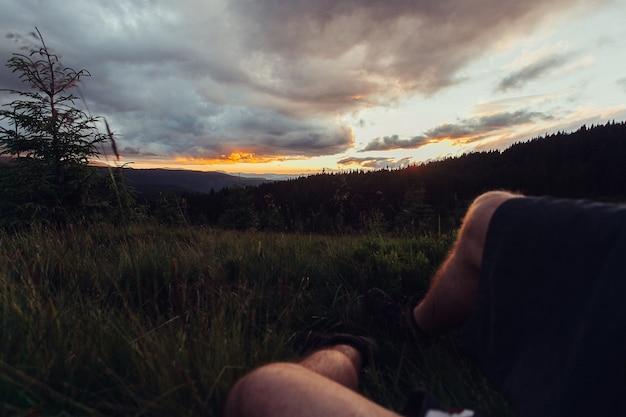 観光、山、ライフスタイル、自然、人々の概念-海の景色の背景に山に横たわる茶色の靴の男性の足