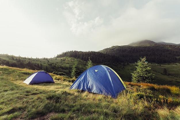 観光、山、ライフスタイル、自然、人々のコンセプト-日の出のフレアと朝の山のテント。